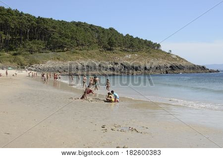 CANGAS DE MORRAZO, SPAIN - AUGUST 9, 2016: People in a summer day in Melide beach located in the natural area of Cabo Home in Cangas de Morrazo in Pontevedra Galicia Spain