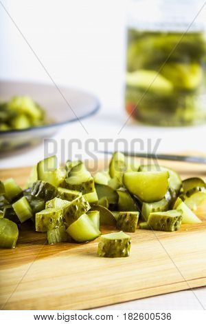 Cucumbers Or Pickled Gherkins With A Knife On A Wooden Cutting Board. White Wooden Background. Bank