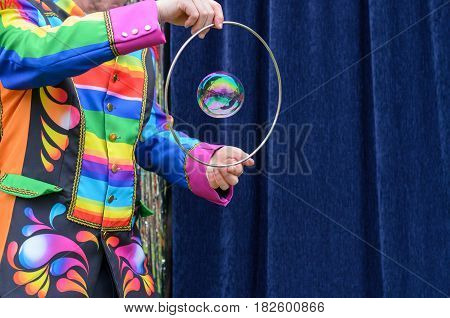 Performer in a bright costume encircling an iridescent sparkling bubble in a ring or hoop held in his hands against a blue curtain with copy space