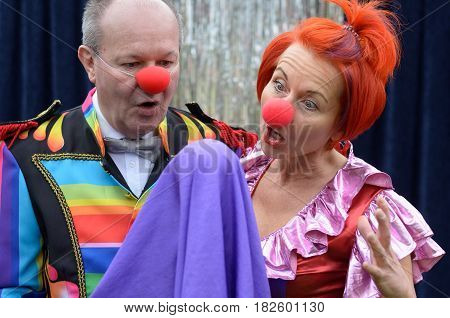 Two red nosed performers in colorful costumes watching an elevating purple cloth around a sphere with mock surprise and shock during a magical stage performance