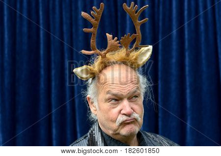 Dubious Man Wearing Gold Reindeer Antlers