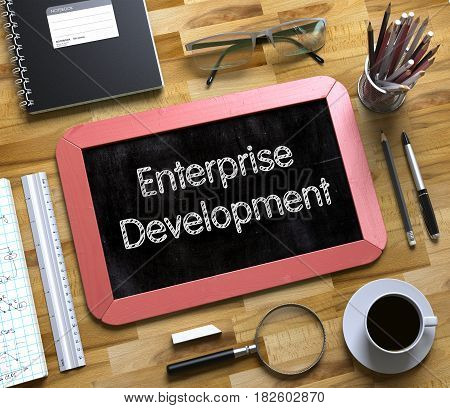 Enterprise Development - Text on Small Chalkboard.Enterprise Development - Red Small Chalkboard with Hand Drawn Text and Stationery on Office Desk. Top View. 3d Rendering.