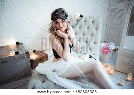 blonde in lingerie in a mask to sleep on the couch