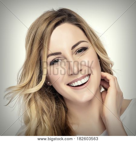 Beautiful young blond smiling woman with clean face. Added toning and vignetting.
