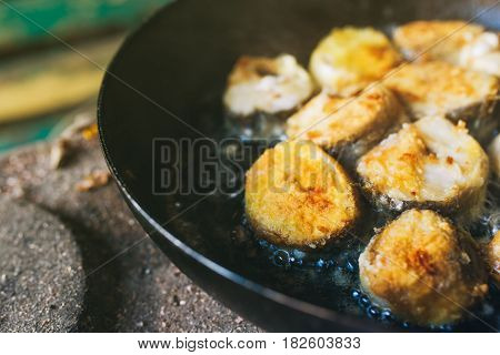 Frying hake fish outdoors on picnic close up of frying pan with oil and fish slices