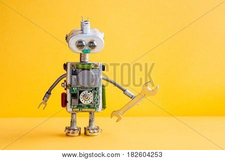 Robot mechanic serviceman with hand wrench. Funny repairman worker, silver iron head, lamp bulb eyes, metallic springs hands, yellow paper background. Copy space.