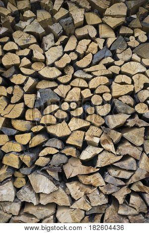 Background texture of wooden chipped logs of different sizes walled