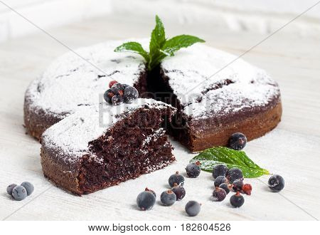 Sliced chocolate pie with mint and ingredients on table. Chocolate pie on wooden table. Country food concept