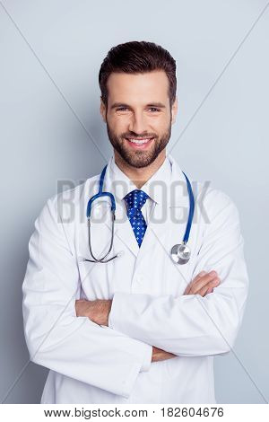 Vertical Photo Of Cheerful Smiling Doc Standing With Crossed Hands Against Gray Background