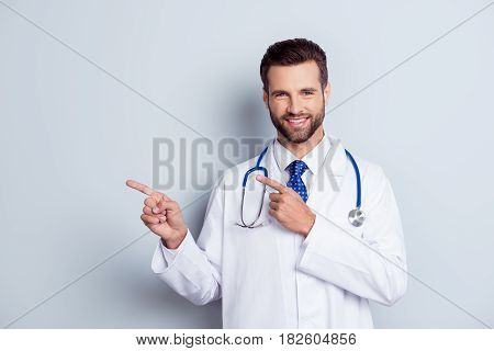 Glad Dentist With Beaming Smile Standing Against White Background And Pointing On Copy-space