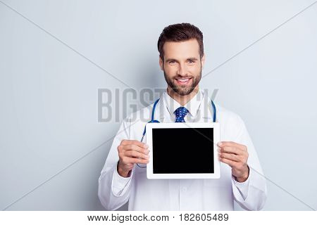 Smart Young Smiling  Doctor In White Coat Demonstrating The Screen Of His Digital Tablet On Gray Bac