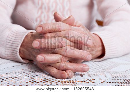 Old hands. Holding hands, horizontally view from front. An elderly woman sits cross-arms at the table at home