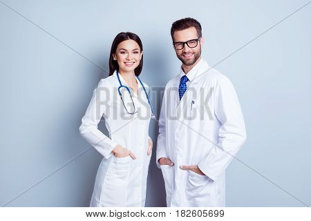 Two Best Smart Professional Smiling Doctors Workers In White Coats Holding Their Hands In Pockets An
