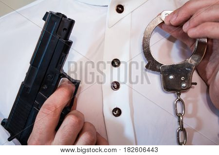 Young Businessman Holds A Handcuff And A Loaded Gun