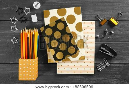 Notebooks and different stationery on wooden background