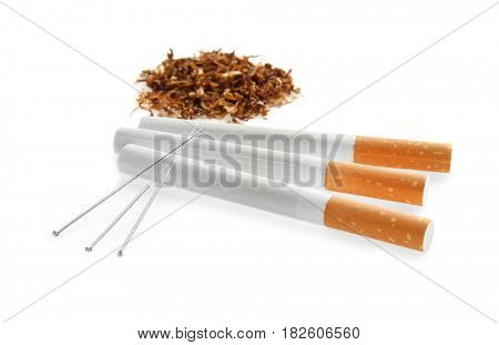 Cigarettes with needles and tobacco on white background