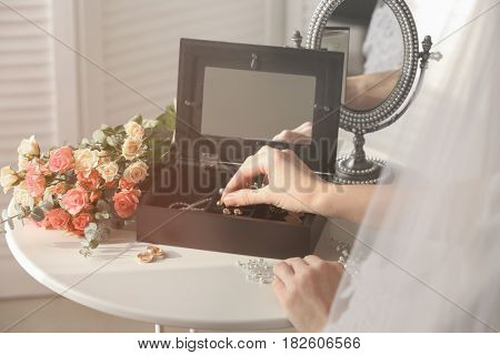 Bride choosing jewelry from box on table