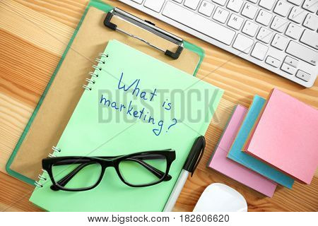 Notebook with text WHAT IS MARKETING on table