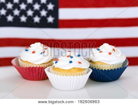 Patriotic cupcakes with American flag in the background.