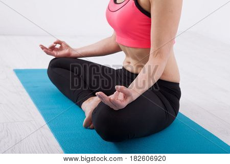 Young beautiful woman doing yoga indoors. Woman sitting in lotus pose with crossed legs in fitness room