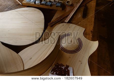 Custom guitar being built in a craftman's workshop with tools and inlay materials