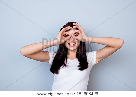 Attractive Young Laughing Woman Having Fun And Making Binoculars Using Her Hands