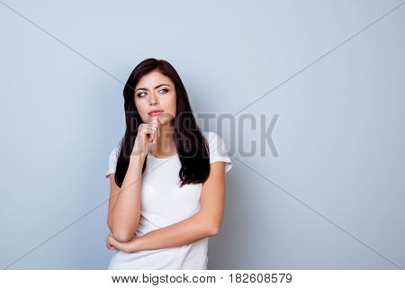 Portrait Of Young Minded Woman In White T-shirt Touching Her Chin Isolated On Gray Background