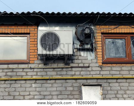 Air conditioning on a brick wall with small windows