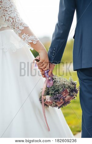 wedding bouquet in hands of newlyweds down