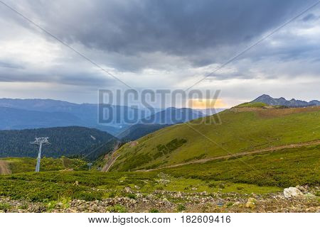 Beautiful mountainscape with cloudy sky and cableway on foreground