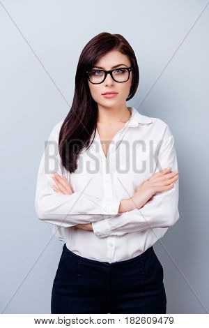 Photo Of Strict Businesswoman In Uniform Standing With Crossed Hands Portrayed On Gray Background