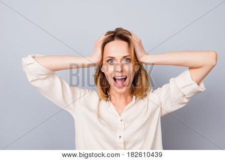Wow! It's Unbelievable! Shocked Happy Woman With Opened Mouth Touching Her Head Isolated On Gray Bac