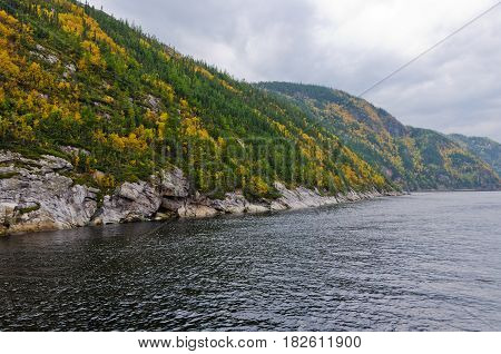Picture of the Saguenay river under dark gray clouds.