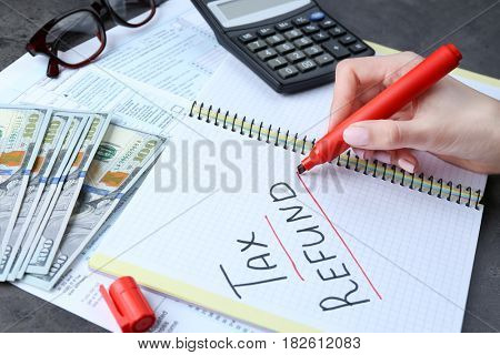 Woman making notes in notebook, closeup. Tax refund concept