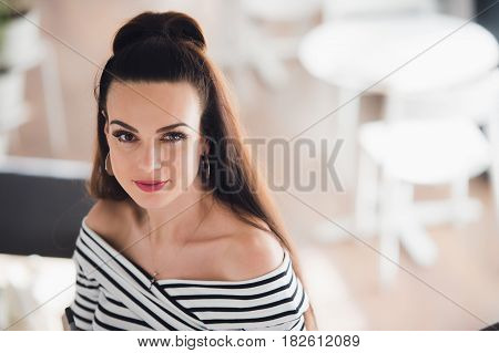 Beautiful woman with brunette hair, sexy smiling female in a cafe, blurred background. She has lovely smile. Stylish look, make up, light pink lipstick, casual outfit, looking at the camera.