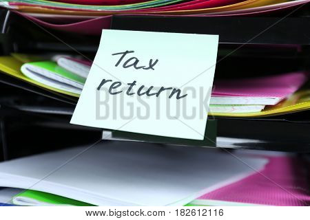 Note with TAX RETURN text attached to paper holder poster