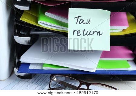 Note with TAX RETURN text and stationery on table