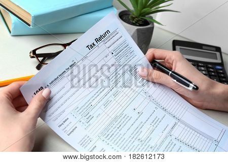 Woman holding individual income tax form, closeup
