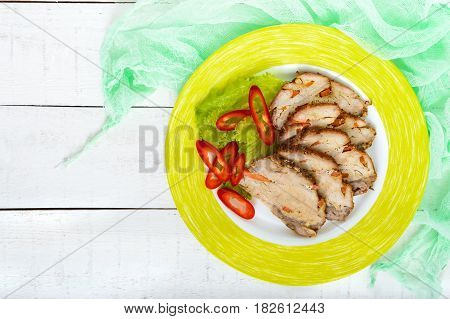 Pork baked ham cutting slices with herbs pepper kapi on a ceramic plate on a white wooden background. The top view.