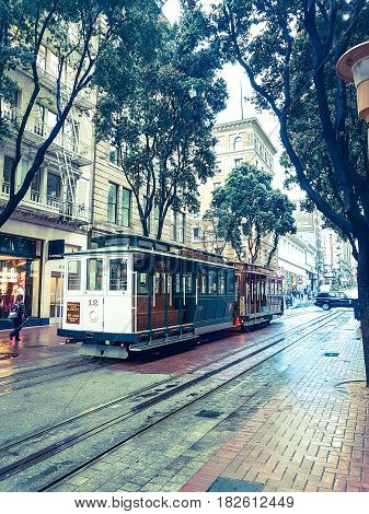 San Francisco, USA - October 28, 2016;Gritty street scene In the city on wet rainy day tram runs along a San Francisco street lined with buildings and trees in old-fashioned effect image.