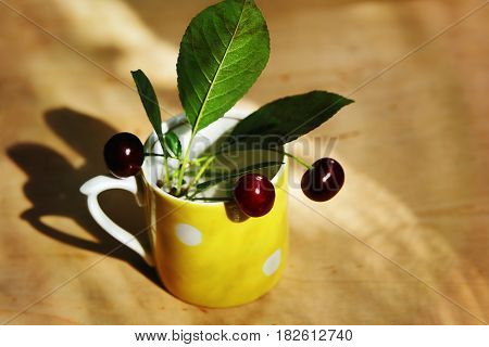 Still life. Cherries in the yellow cup