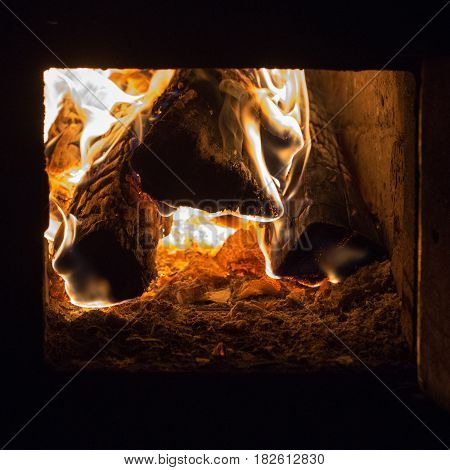 The wood, coal, burning in the fire of the furnace. The night is dark. Black background