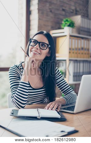 Vertical Portrait Of Positive Smiling Pretty Young Businesswoman Sitting At The Table With A Pencil