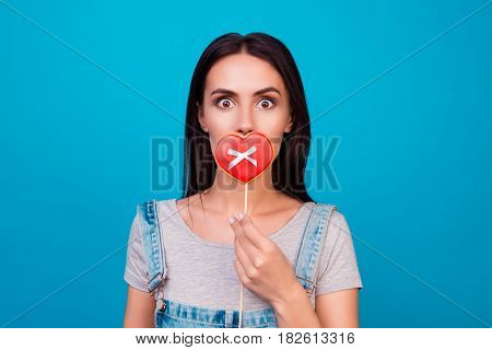 Young Cheerful Woman On Blue Background Closing Her Mouth With Cookie In Shape Of Heart On Blue Back