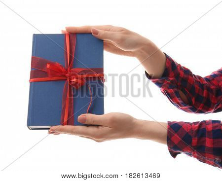 Woman holding book with ribbon as gift on white background