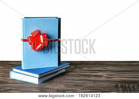Book with ribbon as gift on wooden table