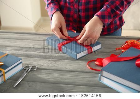 Woman decorating book with ribbon as gift on wooden table
