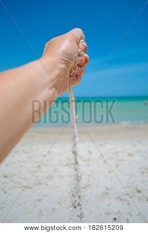Sand running through hand on beach background