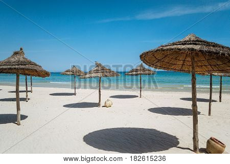 Beach umbrellas on the deserted coast sea on background