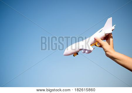 business traveling and vacation. freedom and inspiration. airmail and postal delivery concept. white toy plane in female hand landing or falling on sunny blue sky background copy space
